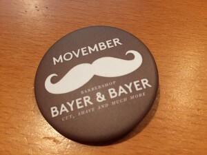 Badge Movember créé par le barbier Bayer & Bayer